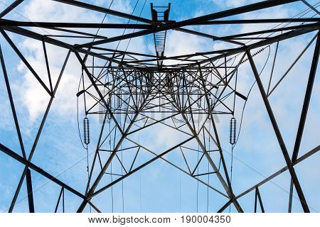 High voltage towers and transmission line at low angle view.
