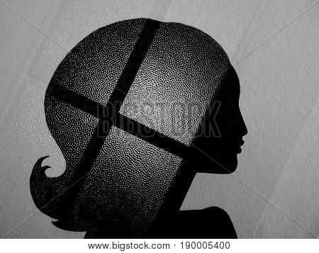 Silhouette of long-haired woman on a grey background. Double Exposure. On the hair is a glass texture with black strips. An unusual profile of a woman. Double exposure, black and white photography