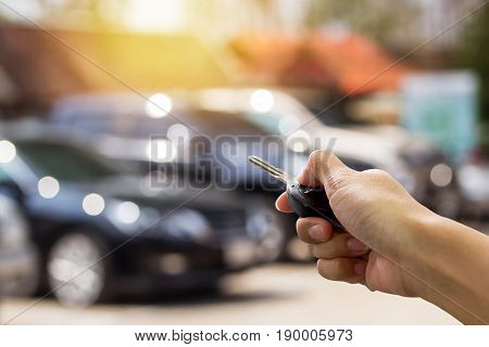 Female hand presses on the remote control car alarm systems with sunlight