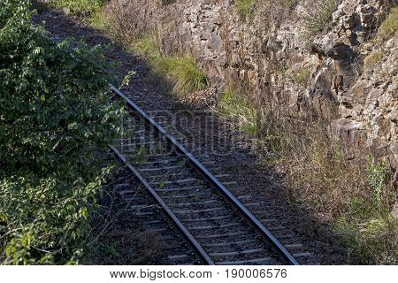 Close up above view of section of railway track and sleepers through natural flora and rocky bank in South Africa