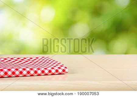 Red checkered cloth on wood table top in green bokeh abstract background - can be used for display or montage your products