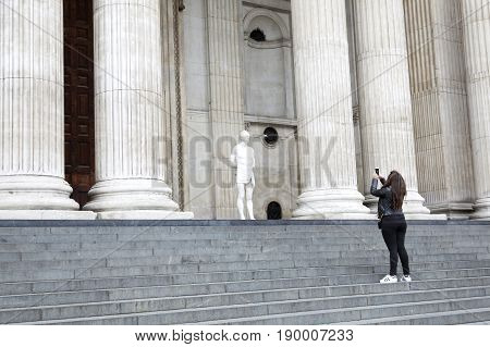 london united kingdom 7 may 2017: girl takes picture of statue christ with barbed wire crown in front of st paul's cathedral in london