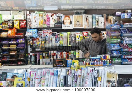 London United Kingdom 7 may 2017: vendor of newspapers and magazines reads while waiting for customers