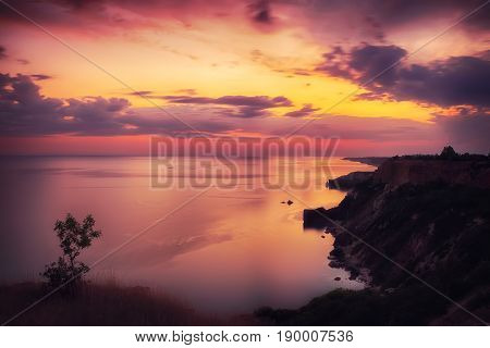 Dramatic sunset at cape fiolent with rocks and grass at foreground. Crimea. Long exposure