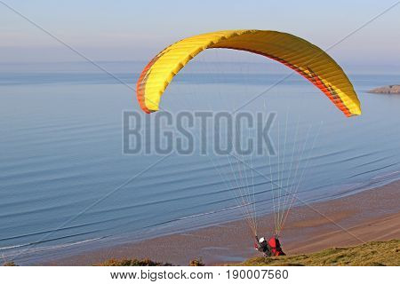 Paraglider launching his wing above Rhossili beach