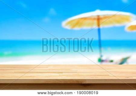 Wood table top on blur white sand beach background summer holiday background concept - can be used for display or montage your products