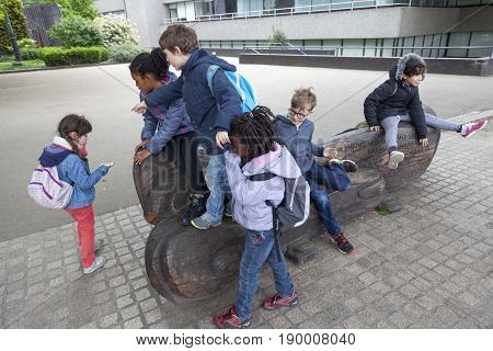 London United Kingdom 6 may 2017: group of school children climb on wooden bench representing river thames on south bank of river thames in london