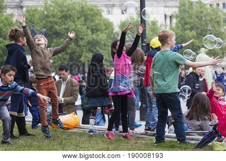 London United Kingdom 6 may 2017: children have fun with giant soap bubbles on trafalgar square in front of national gallery museum