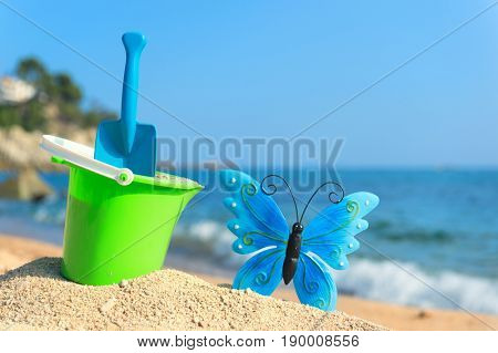 Vacation at the beach coast with toys and butterfly
