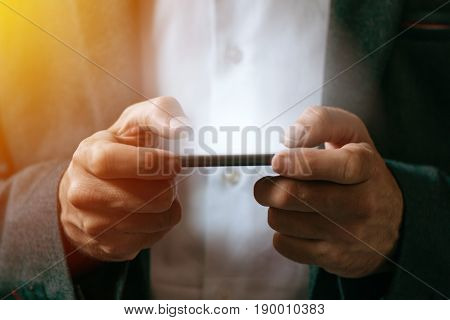 Businessman playing mobile app video game on smart phone close up of male hands