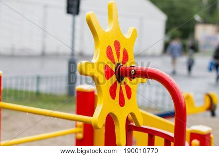The wooden steering wheel is yellow and red in the playground.