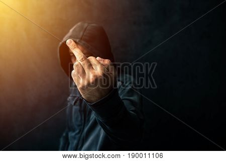 Middle finger rude gesture given by unrecognizable hooded criminal type of person