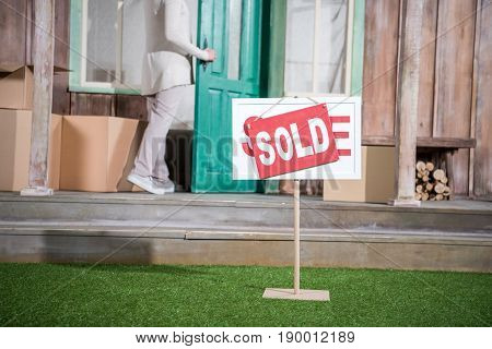 Cropped Shot Of Senior Woman Standing In Doorway Of New House Near Sold Sign On Grass