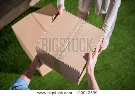 Cropped Shot Of Couple Holding Cardboard Box, Relocation Concept