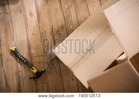 Top view of cardboard boxes with hammer and nails on wooden floor relocation concept