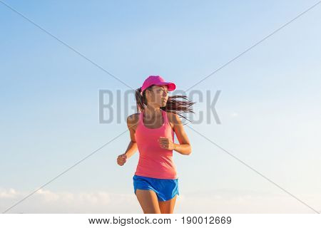 Fitness woman running healthy lifestyle on blue sky background. Empty copyspace.