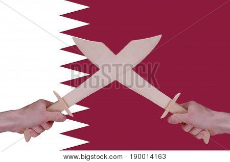 Hands hold crossed wooden sabres, Qatar flag visible on the background.