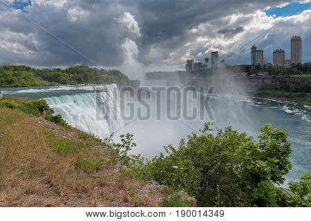 The view of Niagara falls fron American Falls, Horseshoe falls and Canada Skyscrapers on the background.