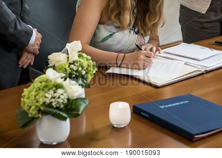 elegant bride signing register, holding pen and official document wedding couple
