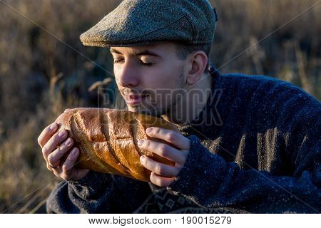 Young guy sniffs fresh bread outdoor on sunset