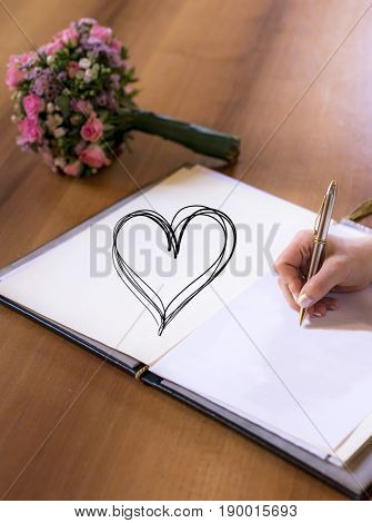 Woman hand writing with pen in a book with heart textspace copyspace wedding flower bouquet