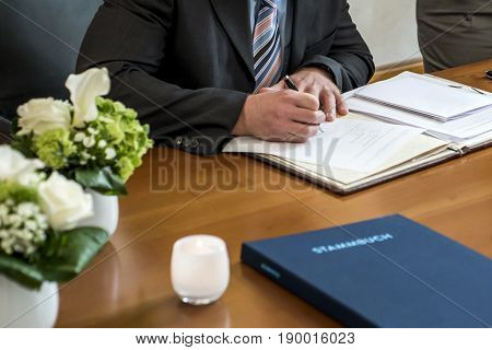 marriage elegant groom signing german wedding register, holding pen and official document couple