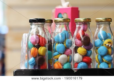 close-up small French colorful macarons in glasses bottle in franch restaurant, famous homemade french dessert