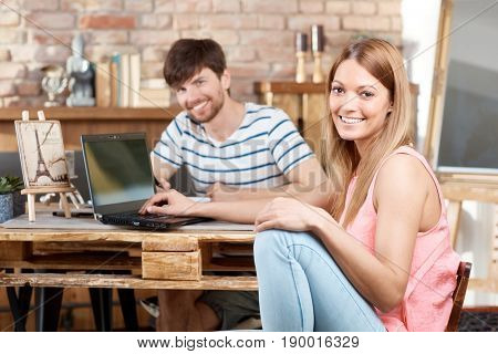 Happy young couple sitting at desk at home, using laptop computer.