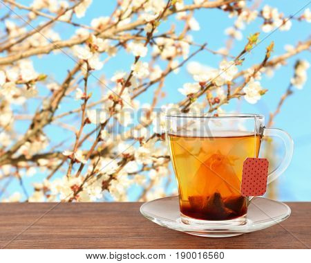 Cup of aromatic tea and blooming branches of apricot tree on background