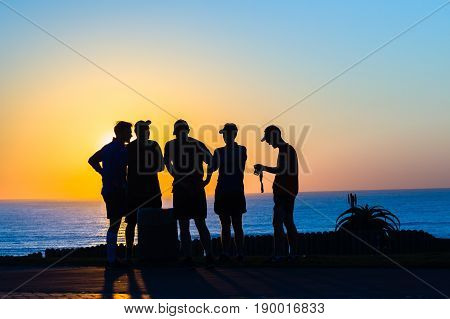 Runners morning talk silhouetted along beach ocean horizon sunrise landscape