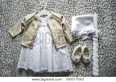 Baby clothes for baptism lying on a floor