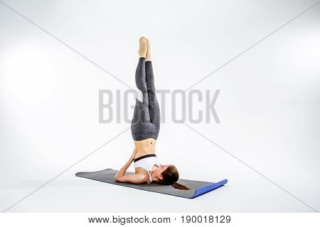 Athlete on rug does exercise, legs up, at empty gray background