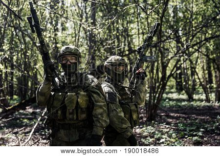 Soldiers with weapons on military mission in forest