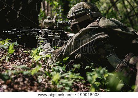 Soldier with submachine gun lies in ambush at forest