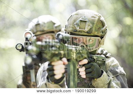 Portrait of two snipers with weapons on military operation in forest