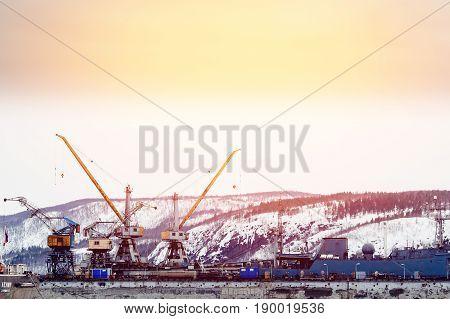 MURMANSK, RUSSIA- APRIL 2, 2017: Embankment along with the river port, the crane unloads coal