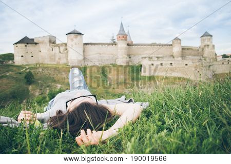 young pretty woman tourist lie in fron of old castle