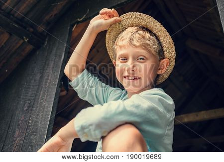 Carefree boy in a straw hat with teeth missing