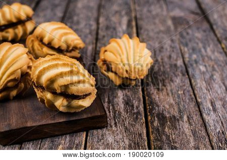 Traditional shortbread cookies with caramel filling on a wooden background. Selective focus.