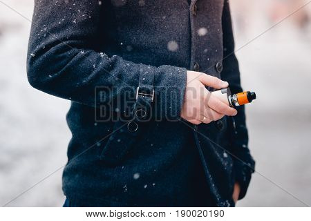 Man holds an electronic cigarette in his hand and exhales steam from his mouth. He is wearing a coat. Winter. The concept is safe for health and cigarettes, nicotine and tobacco.