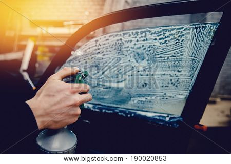 master installs a thin film for the automotive glass, wets the glass from the pulverizer with soapy water. Conceptual car toning