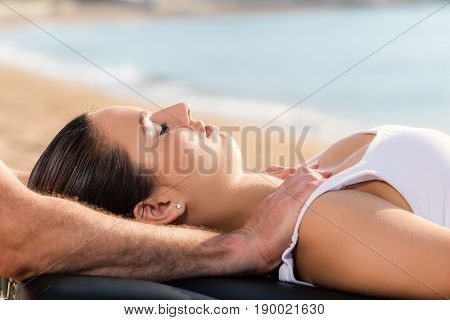 Close up of hands doing osteopathic treatment on young woman outdoors.