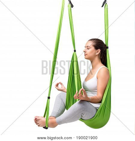 Portrait of young woman doing aerial yoga. Girl sitting with eyes closed in green anti gravity yoga hammock isolated on white background.