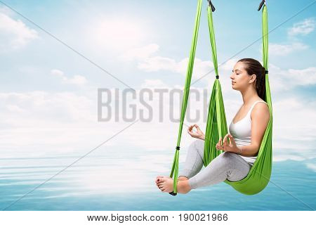 Conceptual portrait of young woman doing aerial yoga over lake. Girl in hanging anti gravity hammock about to touch water surface.