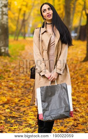 pensive woman standing with packages in hands