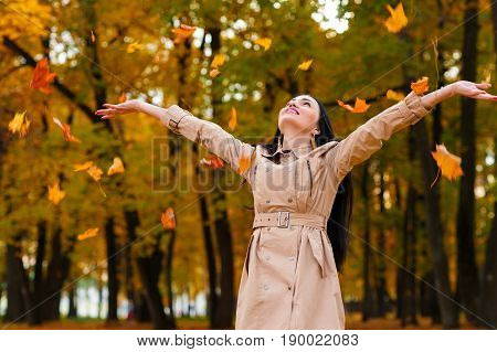 happy woman throws up autumn leaves up