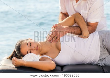 Close up portrait of young woman at osteopathic therapy session outdoors.Osteopath manipulating shoulder and scapula.