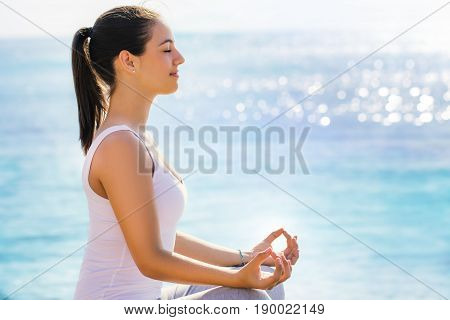 Close up side side view portrait of young woman in casual wear searching for spiritual enlightenment next to sea. Girl doing yoga exercise in early morning sun with bright reflection on water surface.