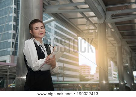 Asian Pretty woman in black dress writing document in rainy day stand on crossing bridge landmark of Bangkok city.