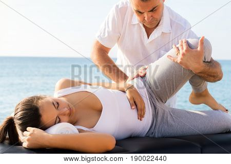 Close up of young woman having osteopathic treatment outdoors. Male therapist doing manipulative articulation massage on leg.